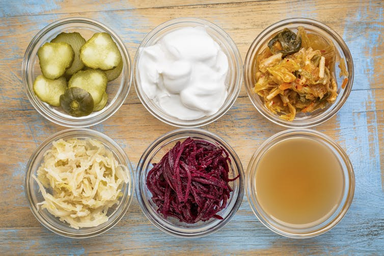 Small glass pots filled with different probiotic foods, such as yoghurt and sauerkraut.