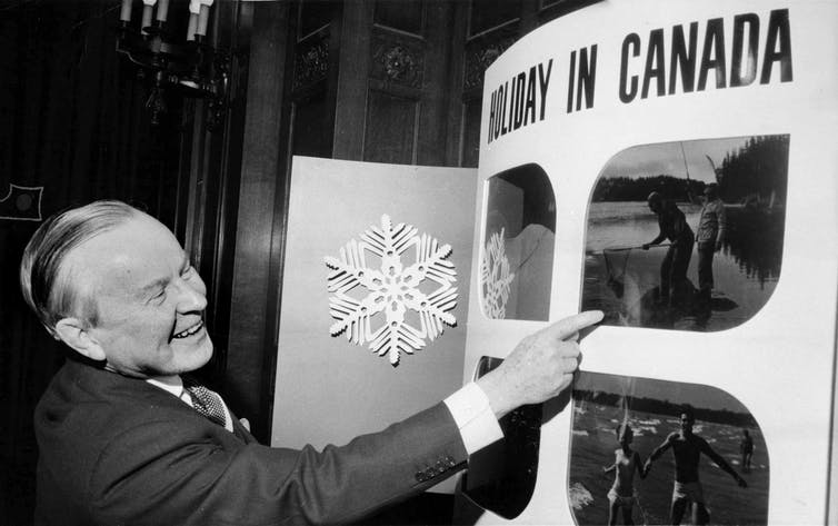 Lester B. Pearson points to a tourism poster.