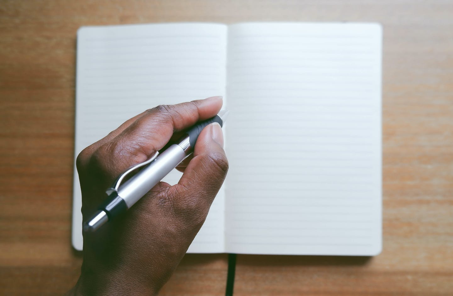 hand with pen poised above empty notebook pages
