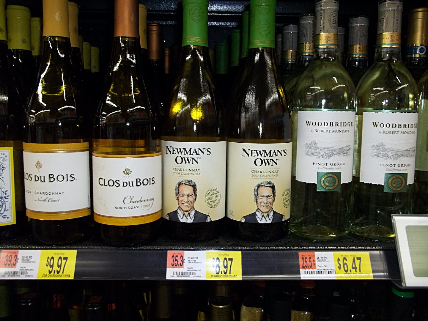 wine bottles on grocery shelf with price labels