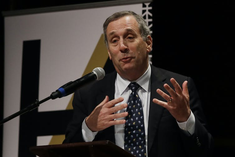 Harvard University President Larry Bacow speaking before a microphone