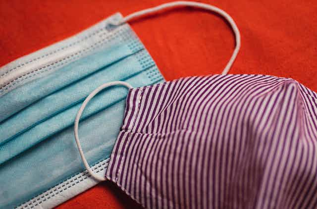 A surgical mask and a cloth mask on a red background.