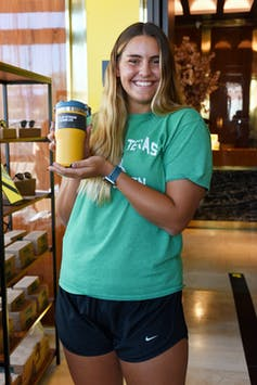 Young woman poses with a coffee tumbler
