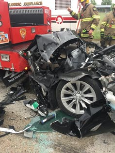 The crumpled front end of a wrecked car against the rear end of a fire engine