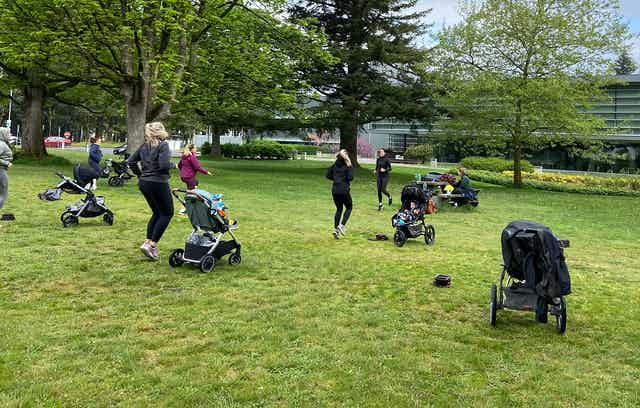 A group of women with infants in strollers exercising in a park