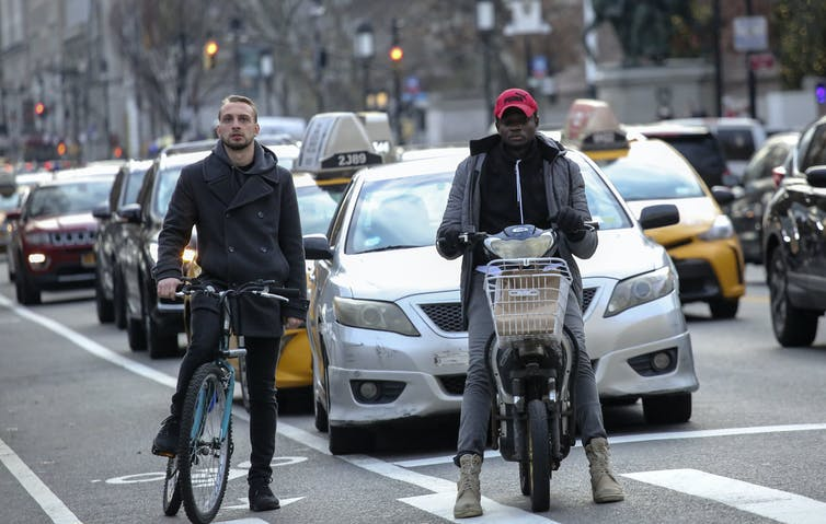 Two men on bicycles wait with taxis at a city stoplight.