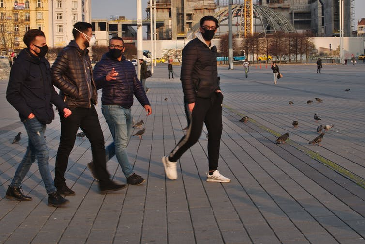 Four Turkish men walk across an open town space.