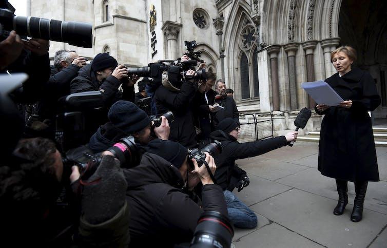 Une femme vêtue de noir lit une déclaration devant une grande foule de photographes et de journalistes