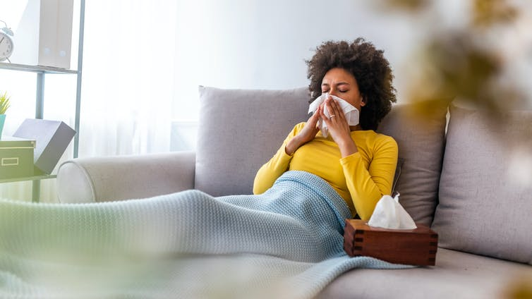 A virus-infected woman blowing her nose