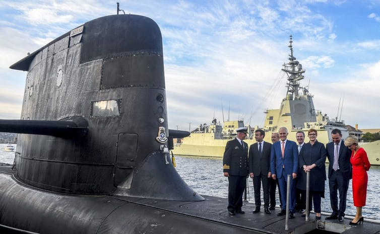 President Emmanuel Macron (2/L) and Australian Prime Minister Malcolm Turnbull (C) standing on the deck of HMAS Waller, a Collins-class submarine operated by the Royal Australian Navy.
