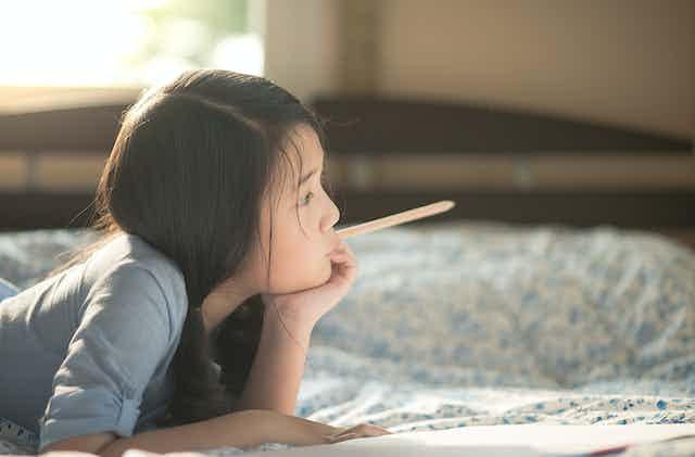Fillette pensive, un crayon à la main, devant un cahier