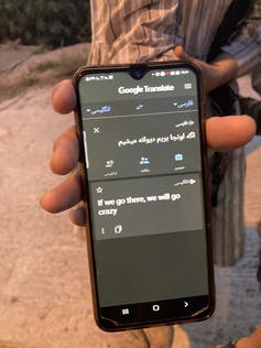 A Woman'S Hand Holds A Cellphone With The Message 'If We Go There, We Will Go Crazy.'