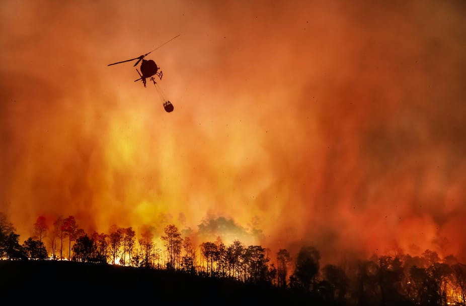 Helicopter with water over a fire.