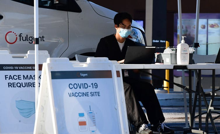 vaccine clinic worker seated at table near signs