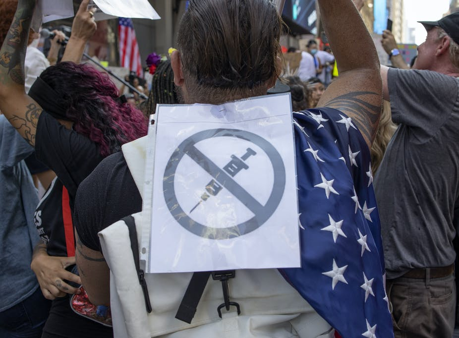 man at a rally with an anti-vaccine sign on his back