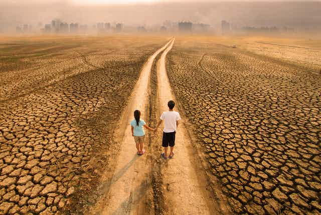 two people standing in a lane in a parched landscape, a city skyline in the distance