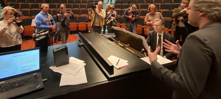 Un grupo de personas de pie alrededor de un pianista.