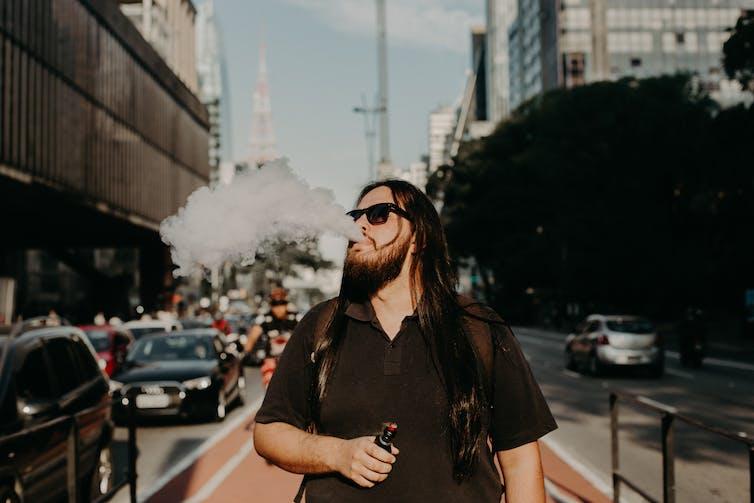 Homme en train de vapoter en marchant dans la rue.