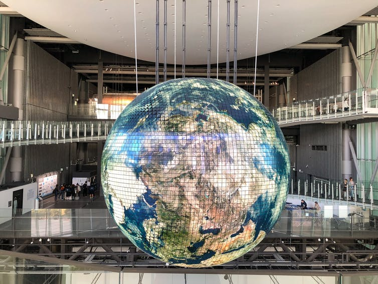 Giant Earth globe hangs in modern building.