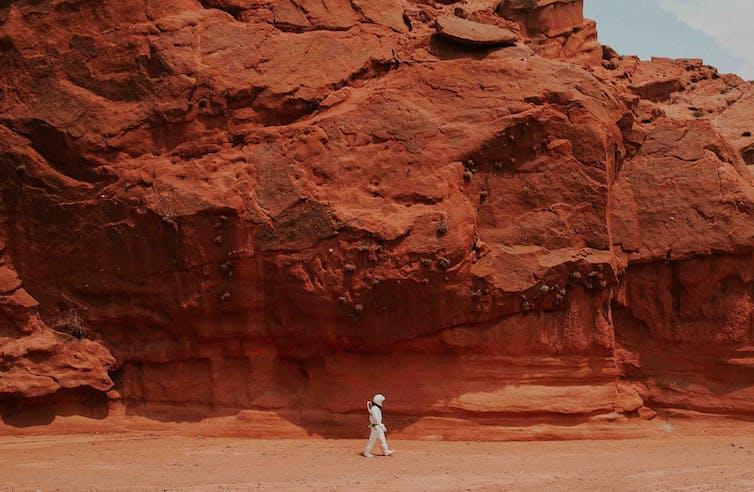 A man in a spacesuit walks across a Martian landscape.