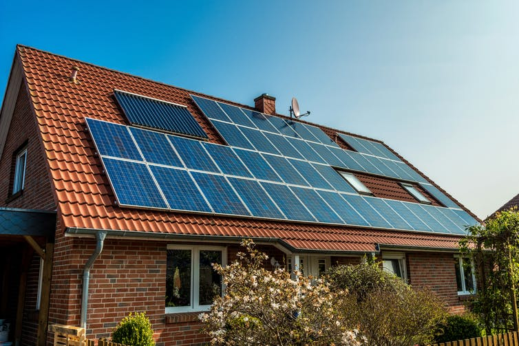 A house with a red tile roof covered in solar panels.