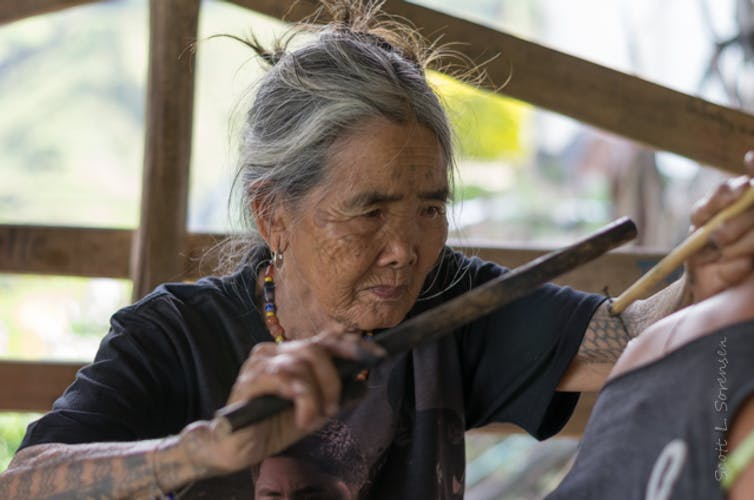 A woman making a traditional mambabatok tattoo using a mallet and needles in the Philippines.