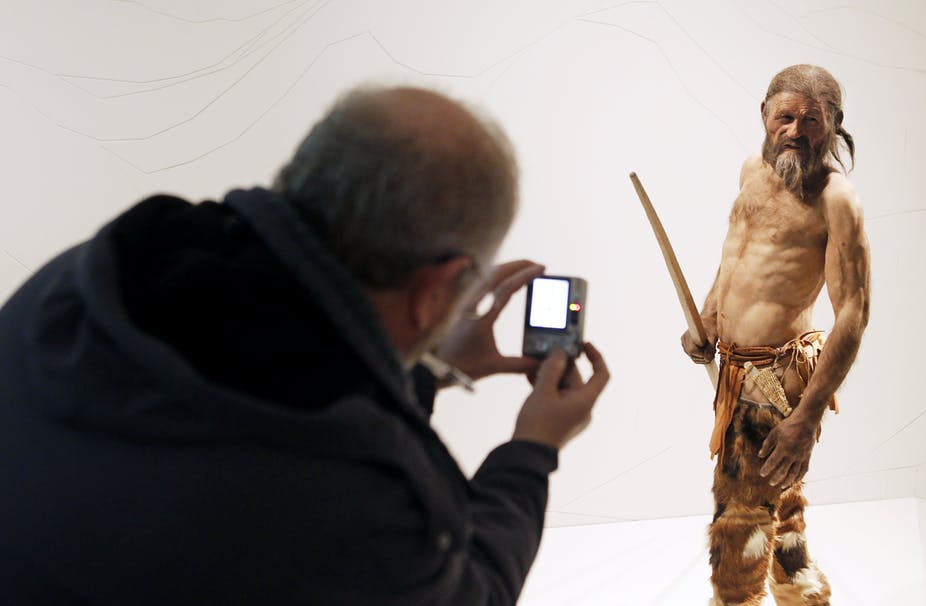 A man takes pictures of a statue representing an iceman named Otzi, discovered in 1991 in the Italian Alps.