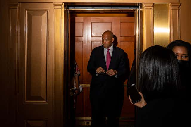 A downbeat looking Senator Cory Booker stands in front of a closed door while journalists wait nearby.