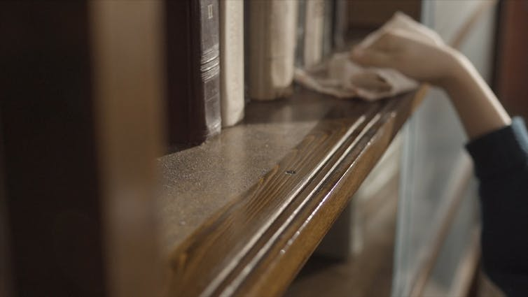 A person wipes dust from a shelf.