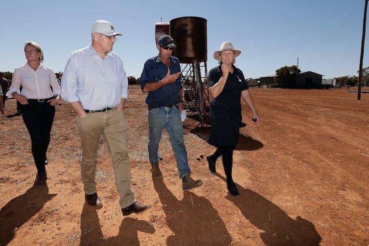 four people walk through dusty farm
