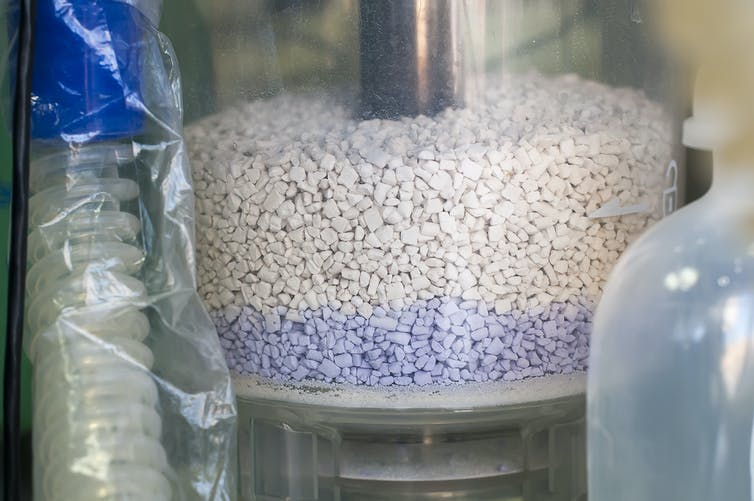 A glass canister containing white and blue gravel.