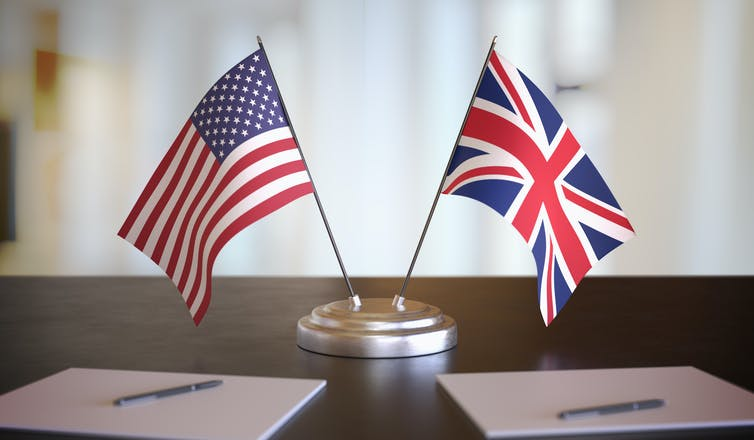 US and UK flags on a desk next to paper and pens.