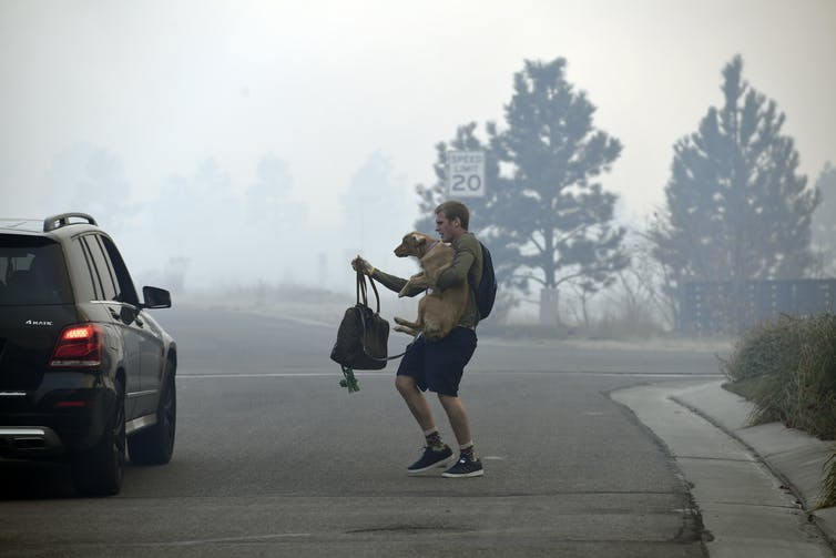 A Man Carried A Dog And Backpack To A Waiting Car In A Smoky Neighborhood As They Prepare To Evacuate From A Wildfire.