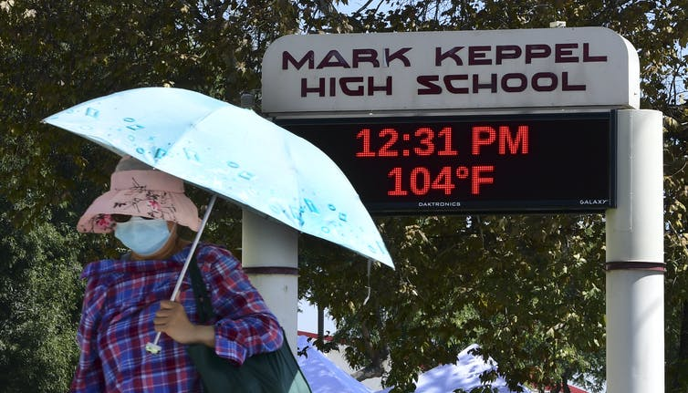 Woman wearing hat and holding umbrella walks by school sign showing temperature is 104 degrees