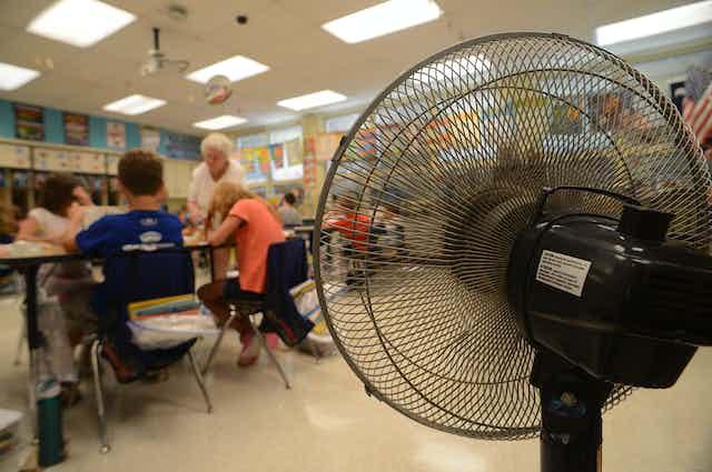 Standing fan blows on students in elementary school classroom