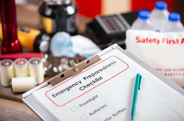 An emergency prep list with items in the background including flashlight, radio, batteries, water