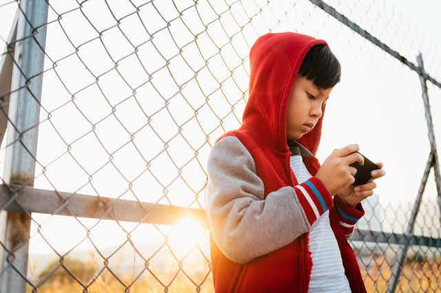 A boy wearing a hooded sweatshirt leans back against a chain-link fence as he holds a smart phone horizontally in both hands and stares at its screen