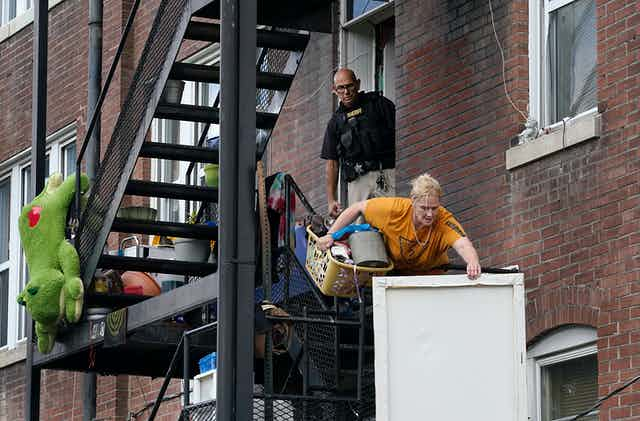 A woman carries a laundry basket full of stuff and a wall picture down a fire escape as a member of the St. Louis sheriff's department watches her eviction.