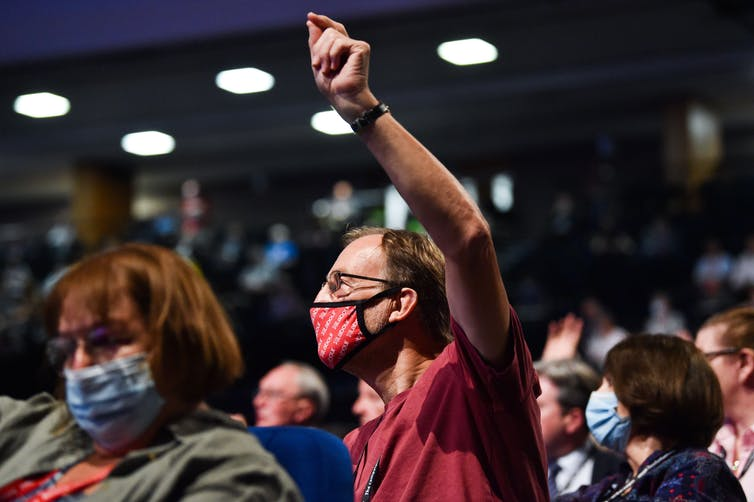 A man wearing a Labour branded face covering holds his hand in the air to vote at party conference.