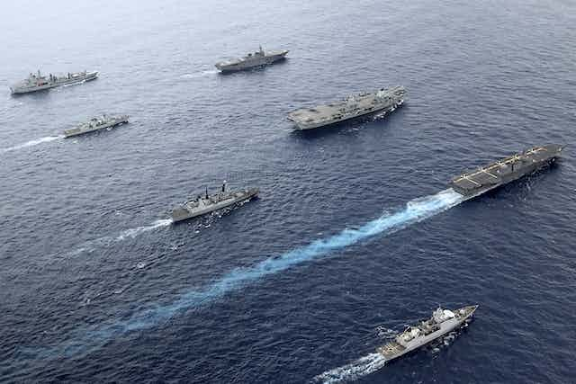 Aircraft carrier and war ships sailing in formation