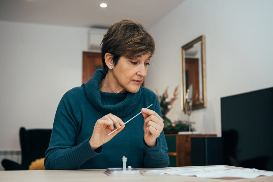 Middle-aged woman with short hair sits at a desk examining the instructions of a home rapid antigen test.