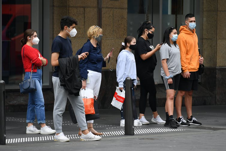 Young people wait at traffic lights to cross the road.
