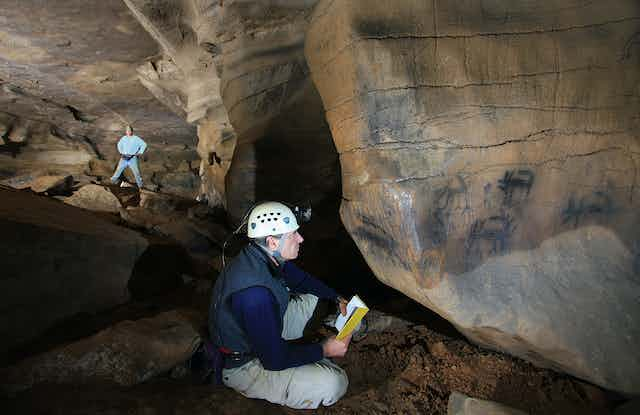 man seated on cave floor looking at black images on stone wall