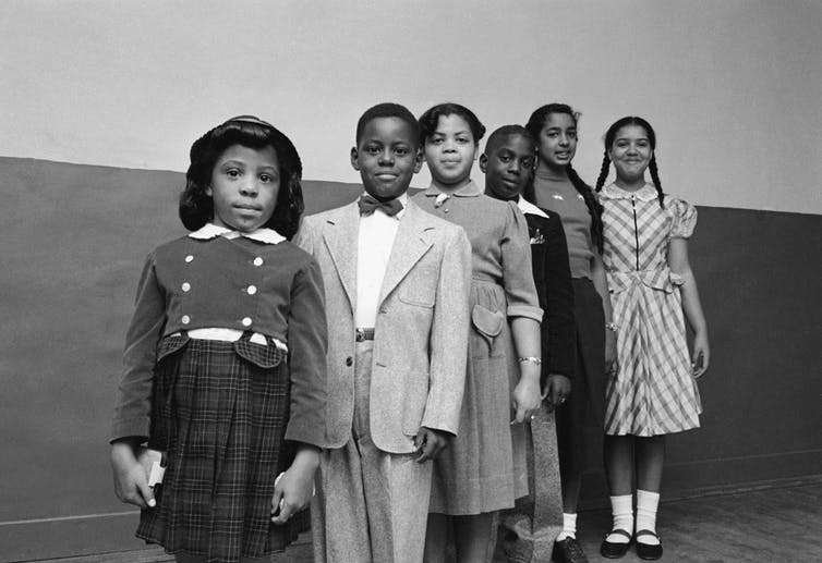 Six Black schoolchildren involved in the Brown v. Board of Education case, dressed up and standing in a line.