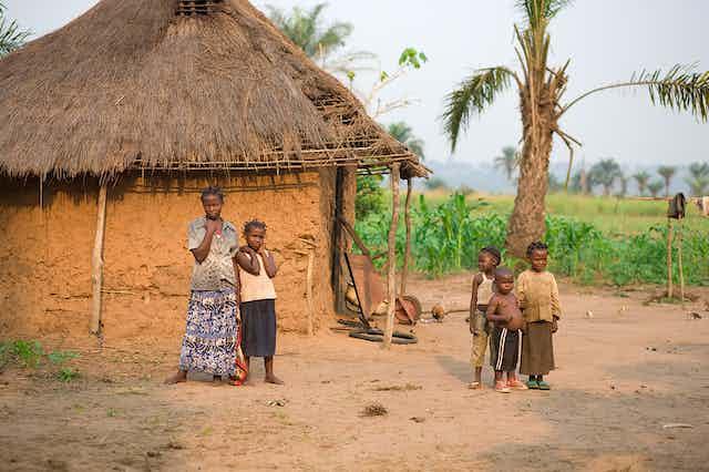 Une femme et des enfants devant leur maison en terre battue