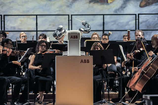 A robot conductor 'performs' in front of an orchestra.
