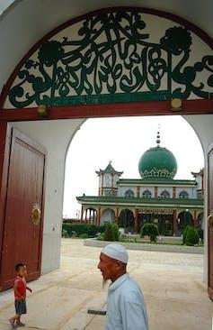 A man walks past a gateway through which can be seen a mosque.