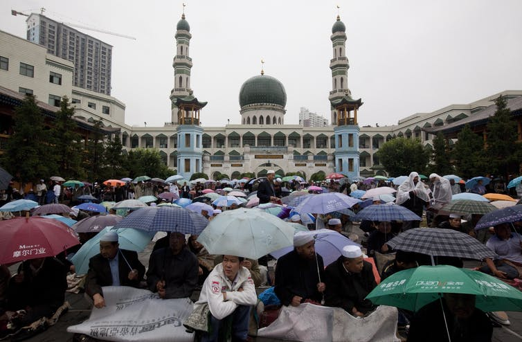 Large crowd under umbrellas outside a mosque.