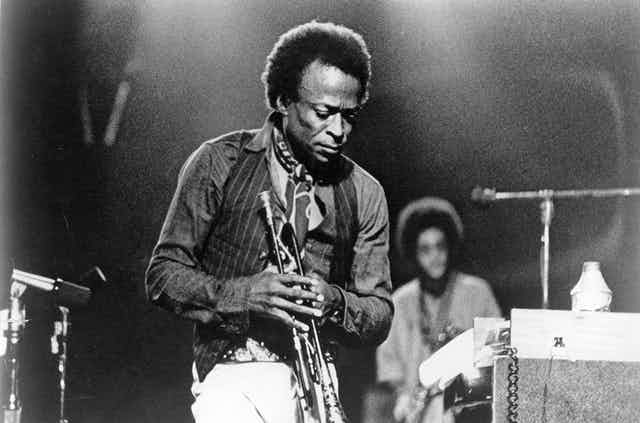 Miles Davis on stage with his trumpet.
