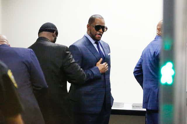 R. Kelly dressed in a suit and sunglasses walks through security checkpoint on the way to court.